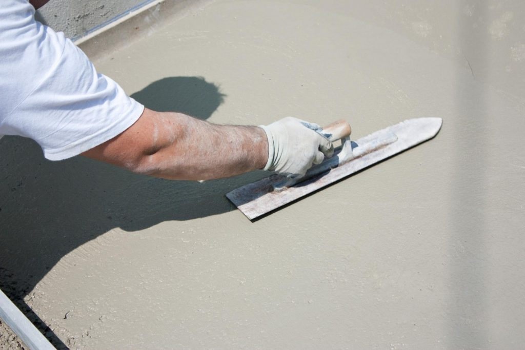 professional concrete worker working on concrete pool deck